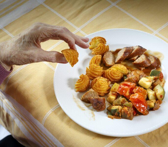 Maaltijd met aardappeltoefjes, worst en groenten
